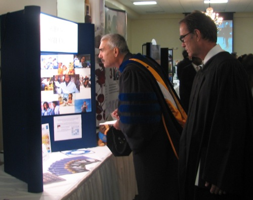 Two distinguished visitors linger over the Aggie Research exhibit at the post-inauguration reception.