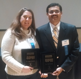 Two outstanding faculty members holding their plaques
